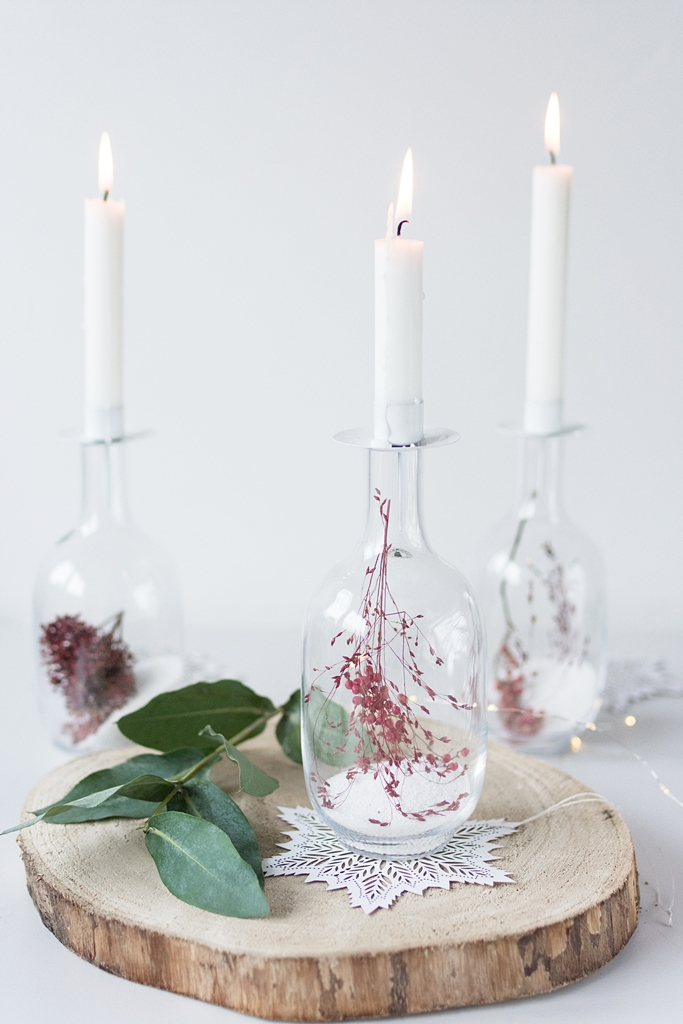 DIY Winterdeko: Befüllte Glasvasen mit getrockneten Beeren und Gräsern als Kerzenhalter
