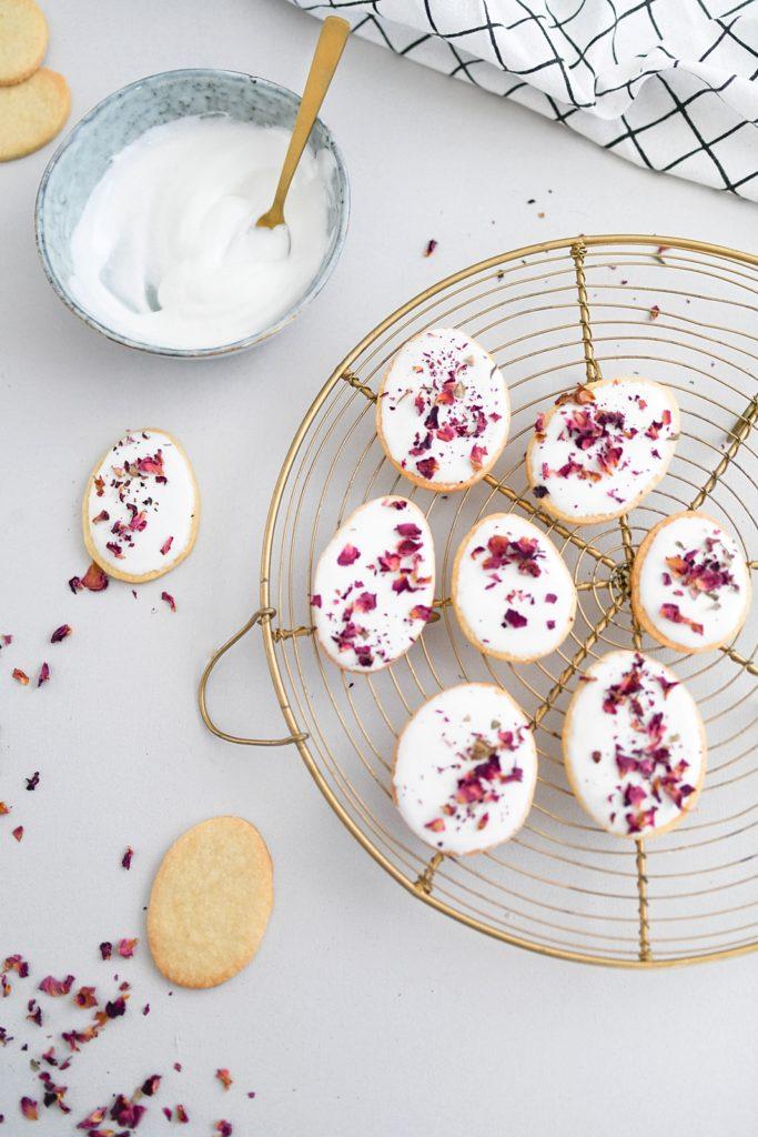 Einfache Osterkekse aus Mürbteig mit Glasur und getrockneten Rosenblüten